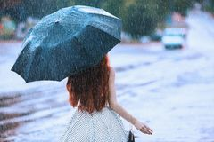 Wet weather. Autumn rain. Lonely girl in polka dots dress hold black umbrella. Raining in city. Wet umbrella against the backdrop. Of the street. Woman was stock photo