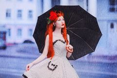 Wet weather. Autumn rain. Lonely girl in polka dots dress hold black umbrella. Raining in city. Wet umbrella against the backdrop royalty free stock images