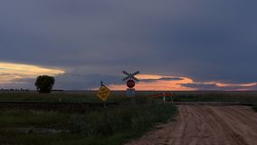 A closed dirt road over a railway crossing with a sunset royalty free stock images