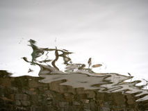 Wet weekend and all that jazz. Artistic background. Rainy reflections of wall and posts, looking like they are dancing or musical Stock Images