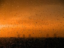 Wet window [3]. Water drops on the window over orange sky Royalty Free Stock Photo