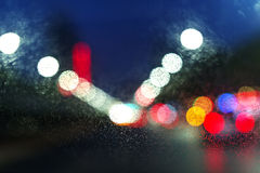 Wet window with background of night city Royalty Free Stock Photos