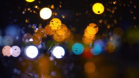 Wet the window with the background of the night city traffic view. Abstract background. Drops of water on the window. Wet the window with the background of the stock video footage