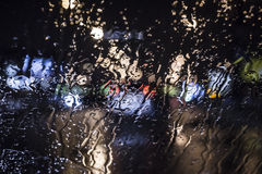 Wet the window with the background of the night city traffic view. Stock Photos
