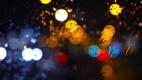 Wet the window with the background of the night city traffic view. Abstract background. Drops of water on the window. Wet the window with the background of the stock video