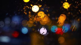 Wet the window with the background of the night city traffic view. Abstract background. Drops of water on the window. Wet the window with the background of the stock footage