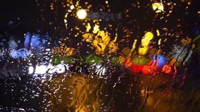 Wet the window with the background of the night city traffic view. Rain On Windscreen, City Blur Background. Moving Bokeh Circles Of Night Traffic stock video
