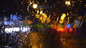 Wet the window with the background of the night city traffic view. Rain On Windscreen, City Blur Background. Moving Bokeh Circles Of Night Traffic stock footage