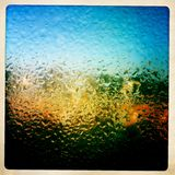 Wet window on the city. Sunlite buildings seen behind a wet window. The condensation creates a beautiful effect. taken with mobile phone Royalty Free Stock Image
