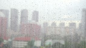 Wet window glass, Rain drops on window glass surface with cloudy blurred city background stock video