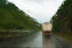 Wet windscreen with heavy rain and track ahead. Low visibility driving concept. Wet windscreen with heavy rain and track on slippery road ahead. Raindrops on stock photo