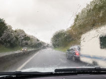 Wet windscreen from rain overtaking car towing a caravan. Royalty Free Stock Image