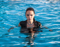 Wet woman in black dress in a swimming pool. Stylish young wet woman in black dress standing in the water in a swimming pool Royalty Free Stock Photo