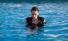 Wet woman in black dress in a swimming pool. Stylish young wet woman in black dress standing in the water in a swimming pool Royalty Free Stock Images