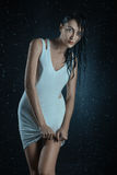 Wet woman in a dress. Wet woman in white dress under water drops Stock Image