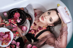 Wet woman with petals and plates. In bath Stock Image