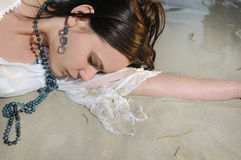 Wet woman on the sand. Portrait of young wet woman laying on the sand Royalty Free Stock Image