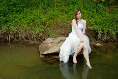 Wet Woman Sitting On A Rock Over The Water Stock Photo