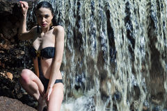Wet woman in swimsuit on waterfall Stock Photography