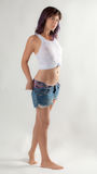 Wet Woman in Tied Tank Top Undressing. An image of a young, fit woman in a cropped top taking off her jean shorts Stock Images