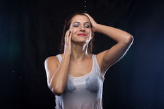 Wet woman in white t-shirt touching hair Stock Images