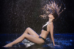 Wet women. Beautiful wet woman in black bikini sitting on the floor under the rain Royalty Free Stock Photography