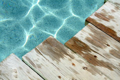 Wet Wood. Planks of wet wood and a beautiful swimming pool with reflections Stock Photo