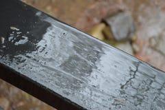 Wet wood, black railing. Garden. Rainy day Royalty Free Stock Photography