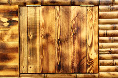 Wet yellow brown closed wooden door in bamboo wall Royalty Free Stock Image