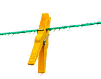 Wet yellow clothespin on a washing line. Wet yellow clothespin on a green washing line full of rain drops Royalty Free Stock Images