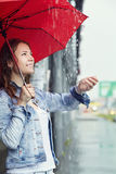 Wet young girl in the rain. Portrait of a wet young girl walking in the rain with an umbrella Royalty Free Stock Images