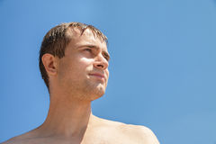 Wet young man on blue sky background Royalty Free Stock Image