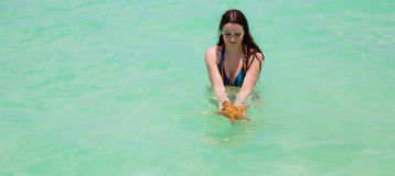 Wet young woman with super long hair in turquoise sea water holding big starfish in hands. Wet young woman with super long hair in turquoise sea water holding Royalty Free Stock Image