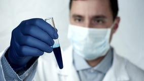 Wetenschappelijk onderzoeker, Arts Looking bij Blauwe Oplossing in Reageerbuis in Laboratorium stock video