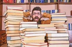 Wetenschappelijk ontdekkingsconcept Mens op geschokt gezicht tussen stapels van boeken in bibliotheek, boekenrekken op achtergron royalty-vrije stock fotografie
