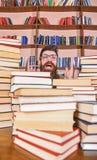 Wetenschappelijk ontdekkingsconcept Mens op opgewekt gezicht tussen stapels van boeken in bibliotheek, boekenrekken op achtergron royalty-vrije stock afbeelding