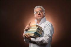 Wetenschappelijke denker, filosofie, bejaarde grijs-haired mens in een wit overhemd met boeken, met studiolicht royalty-vrije stock afbeelding