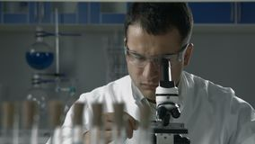 Wetenschappelijke onderzoeker die microscoop in het laboratorium gebruiken stock video