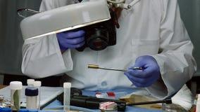 Wetenschappelijke politie die en foto's van een kogel GLB in ballistisch Laboratorium onderzoeken maken stock video