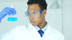 Wetenschapper, arts die blauwe oplossing in fles in laboratorium bekijken stock videobeelden