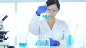 Wetenschapper, arts die blauwe oplossing in fles in laboratorium bekijken stock footage
