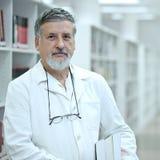 Wetenschapper/arts in een bibliotheek Stock Foto
