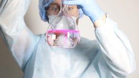 Wetenschapper arts in medische eenvormig, houdend fles en lettend op de vooruitgang van experiment stock video