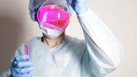 Wetenschapper arts in medische eenvormig, houdend fles en lettend op de vooruitgang van experiment stock footage