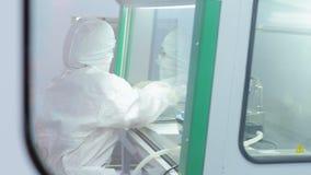 Wetenschapper in beschermend kostuum die bij laboratorium werken Farmacologische technologieën stock footage