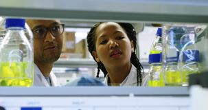 Wetenschapper die chemische oplossing 4k bekijken stock videobeelden