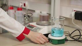 Wetenschapper die chemische vloeistof in reageerbuizen laten vallen stock footage