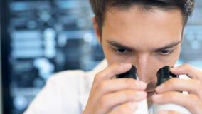 Wetenschapper die door een microscoop in een laboratorium kijken stock videobeelden