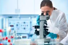 Wetenschapper die door een microscoop kijkt Royalty-vrije Stock Afbeelding