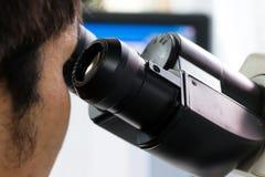 Wetenschapper die door een microscoop kijkt Stock Foto